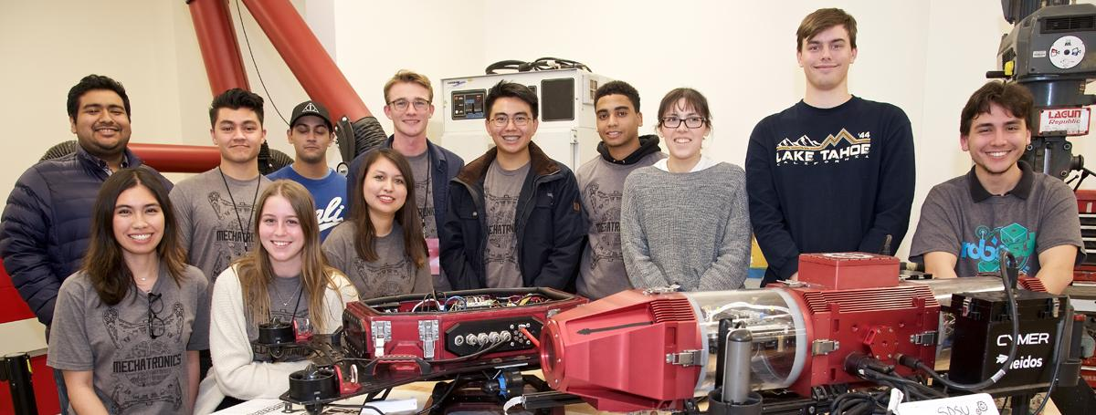 Team members from SDSU Mechatronics student club standing in front of robosub.