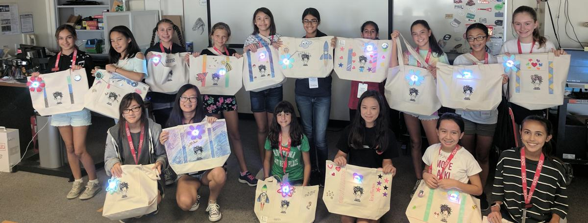 16 female students standing in classroom with tote bags created at Tech Camp