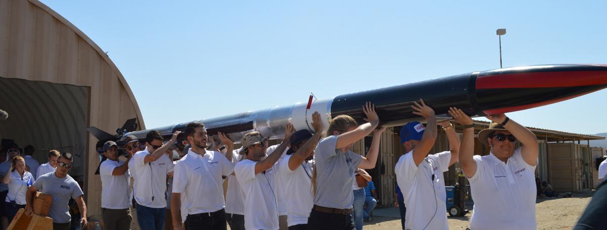 Aerospace students carrying rocket