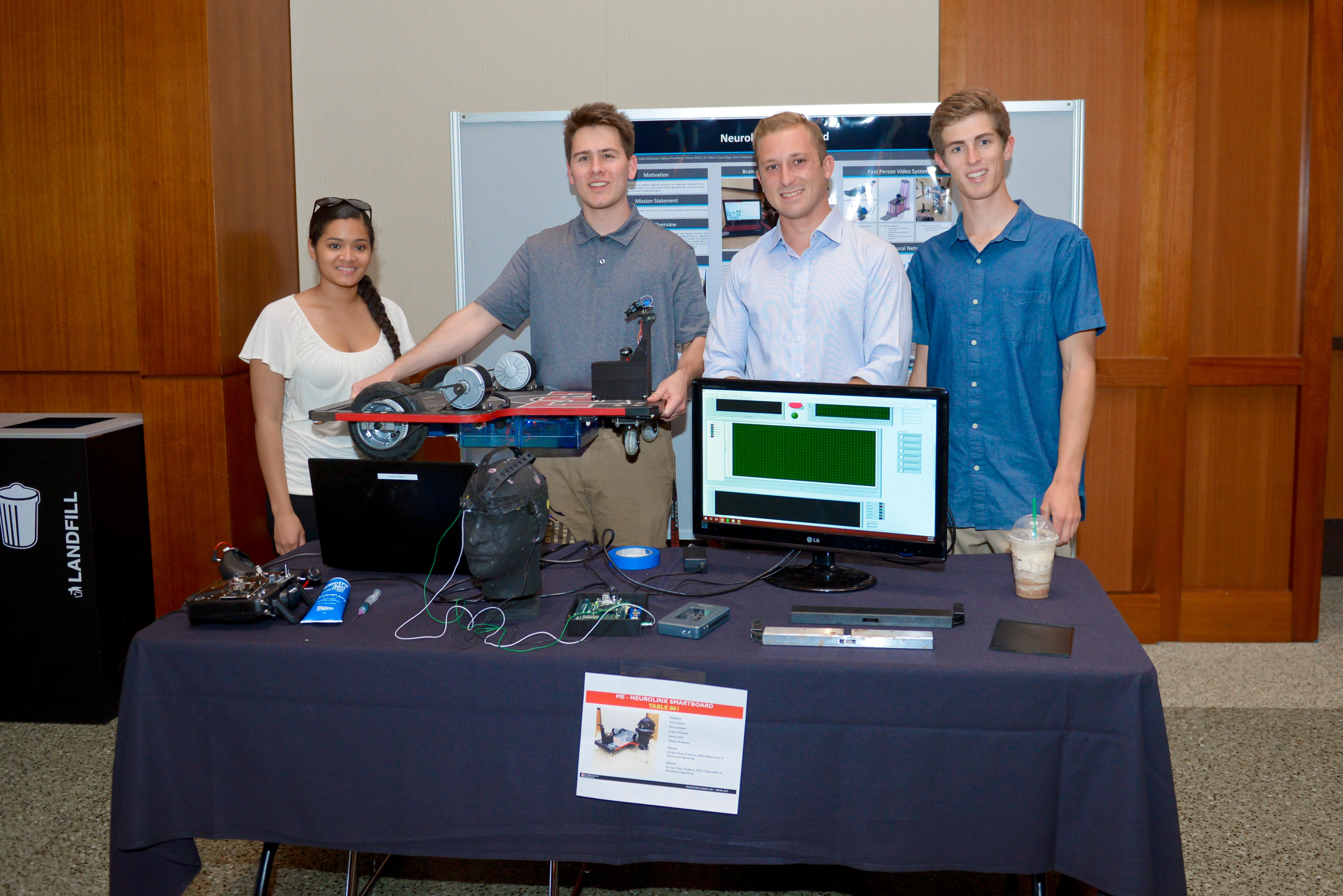 Four students displaying their computer and project